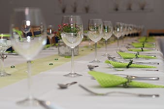 Selective focus photography of wine glasses and forks with table napkins