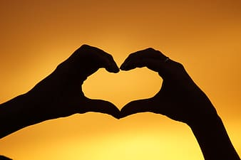 Silhouette of two hands forming heart