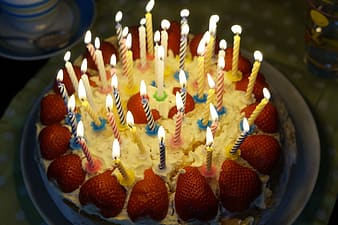 White icing cake with strawberry topping and in-lighted candles