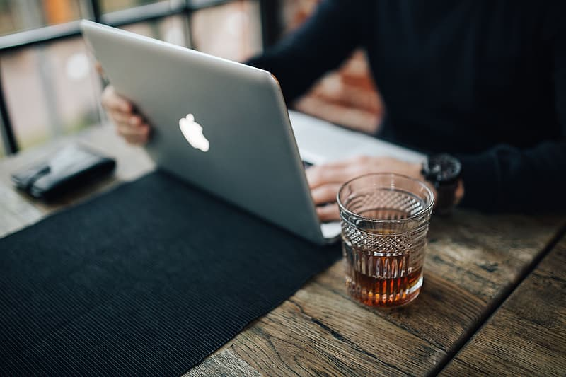 Silver macbook beside clear drinking glass on black table