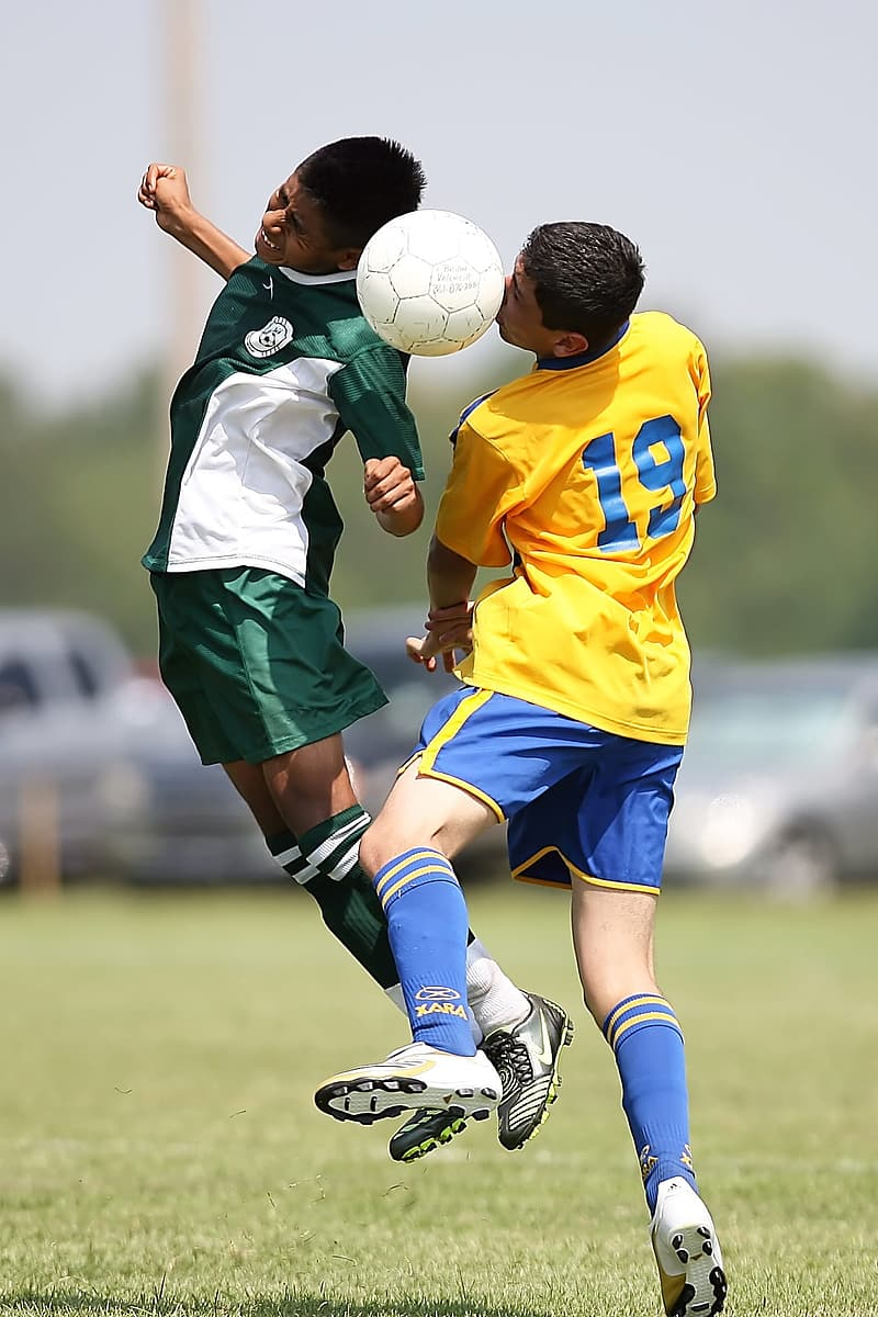 Two soccer players heading a soccer ball in field