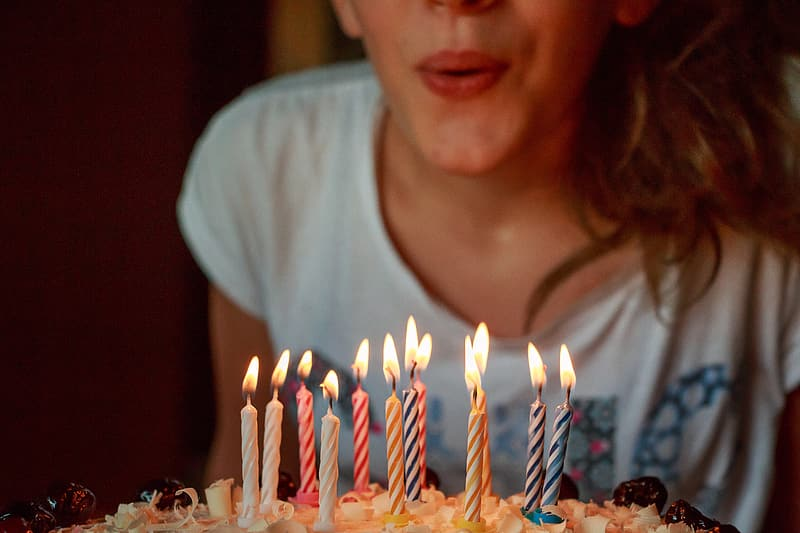Woman wearin ggray printed shirt blowing candle in cake