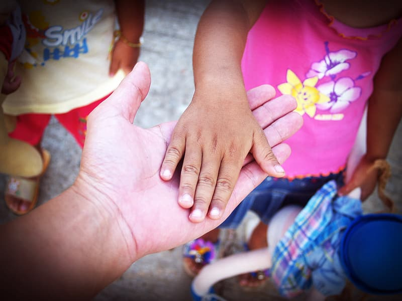Focus photography of person of man holding hand of girl during daytime