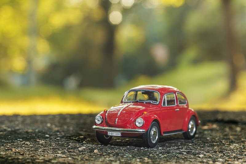 Stilt shift red Volkswagen Beetle scale model selective focus photography