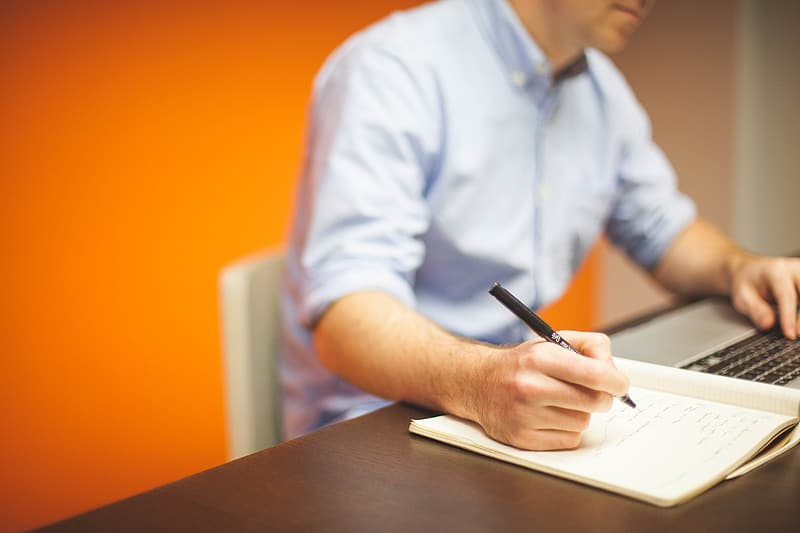 Person in white dress shirt writing on white paper