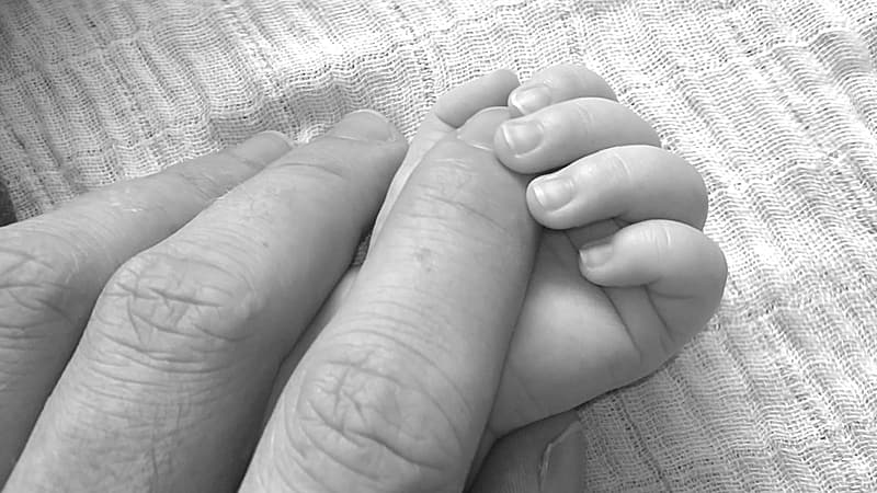 Person hand over baby hand