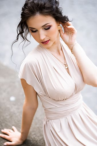 Woman in white dress holding her hair
