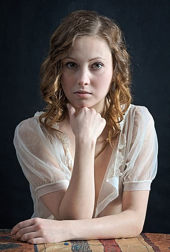 Woman wearing white see through shirt resting her hand on her chin