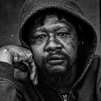 Grayscaled photo of man wearing hoodie
