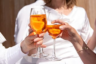 2 person holding clear wine glasses
