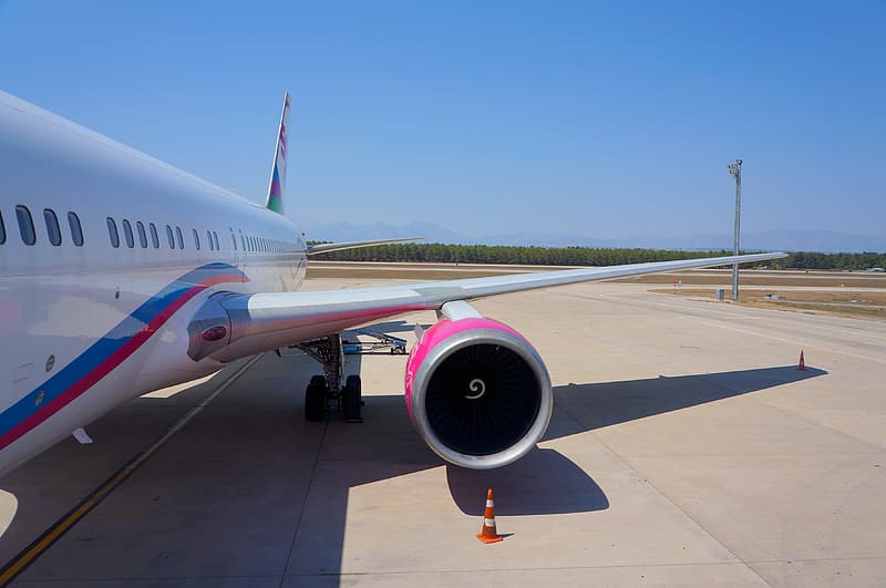 White and pink airplane on airport during daytime