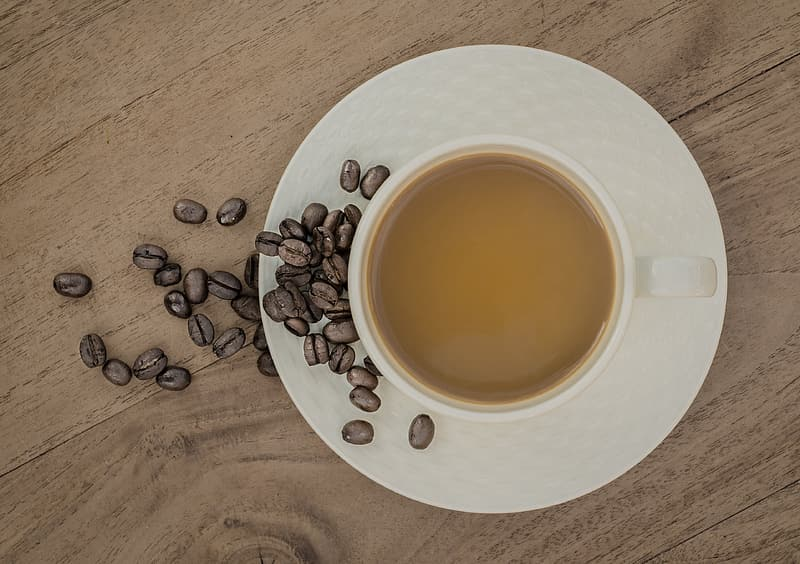 Flat lay photography of cup of coffee with coffee beans