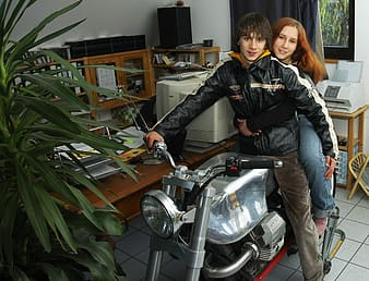 Man and woman riding motorcycle indoors