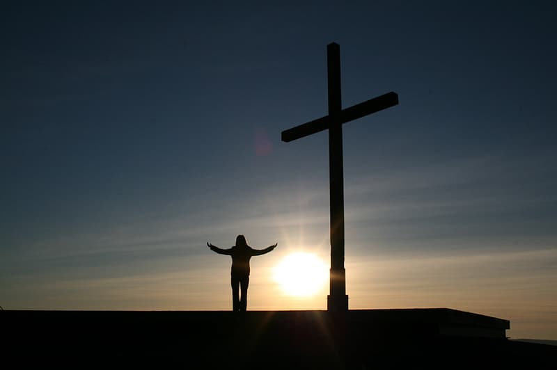 Silhouette person standing beside of crucifix statute