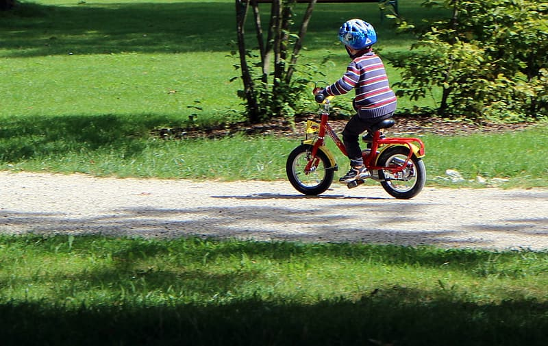 Boy wearing helmet riding red bicycle on road during daytime