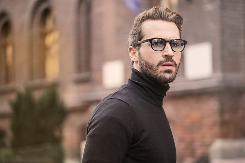 Young bearded male wearing black turtleneck top and eyeglasses posing at the street