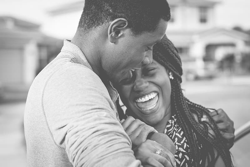 Grayscale photo of man hugging woman laughing each other