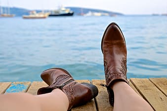 Woman wearing brown leather boots near body of water and boats at daytime
