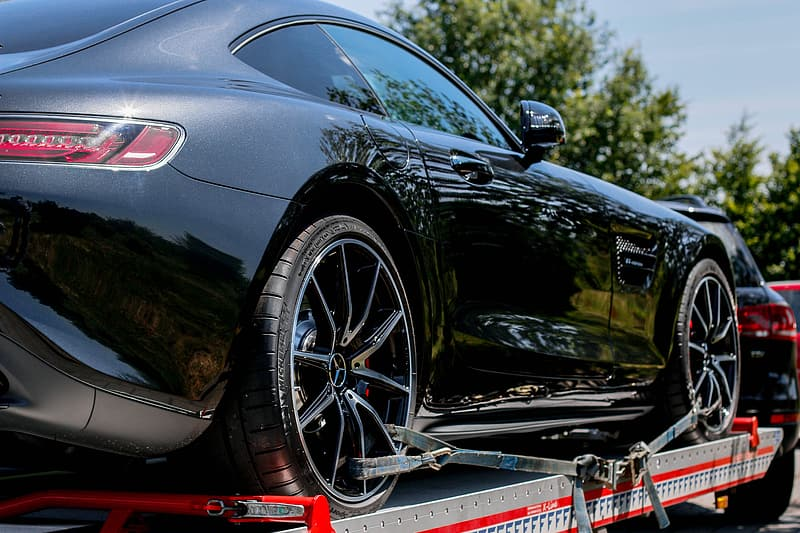 Black Mercedes-Benz AMG GT on metal trailer attached to black SUV during daytime