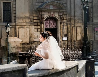 Woman in white wedding dress sitting on gray concrete bench