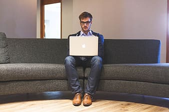 Man sitting on sofa with MacBook on his lap