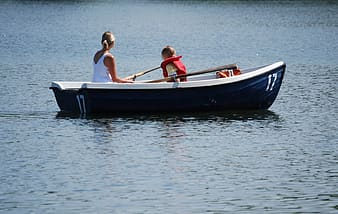 Woman and girl riding boat on body of water