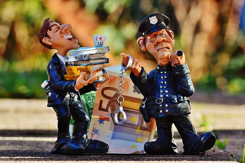 Man holding stock of books near policeman holding handcuffs near 50 Euro figurine