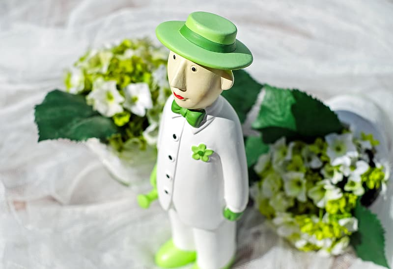 Male character wearing white button-up jacket figurine near white petaled flower bouquet