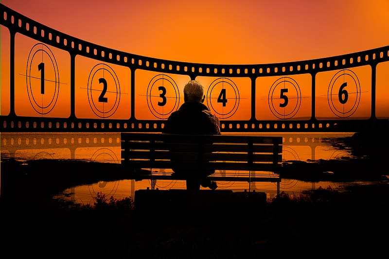 Silhouette of person standing on bridge during sunset