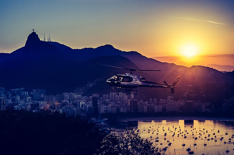 White and black helicopter flying over the city during sunset