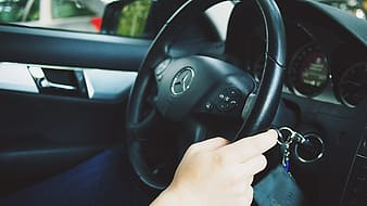 Person driving Mercedes-Benz vehicle at daytime