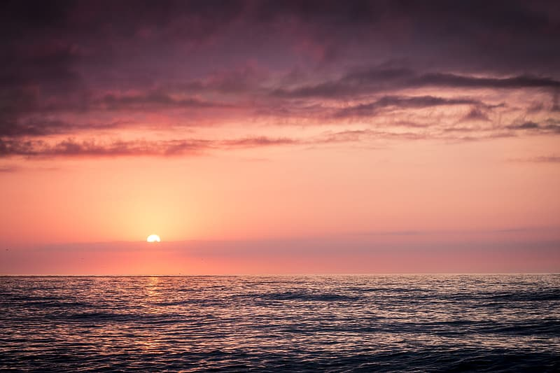Camly body of water under cloudy sky at sunset