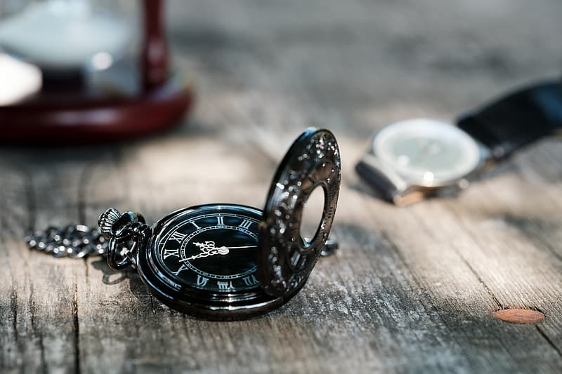 Silver-colored pocket watch on wooden board