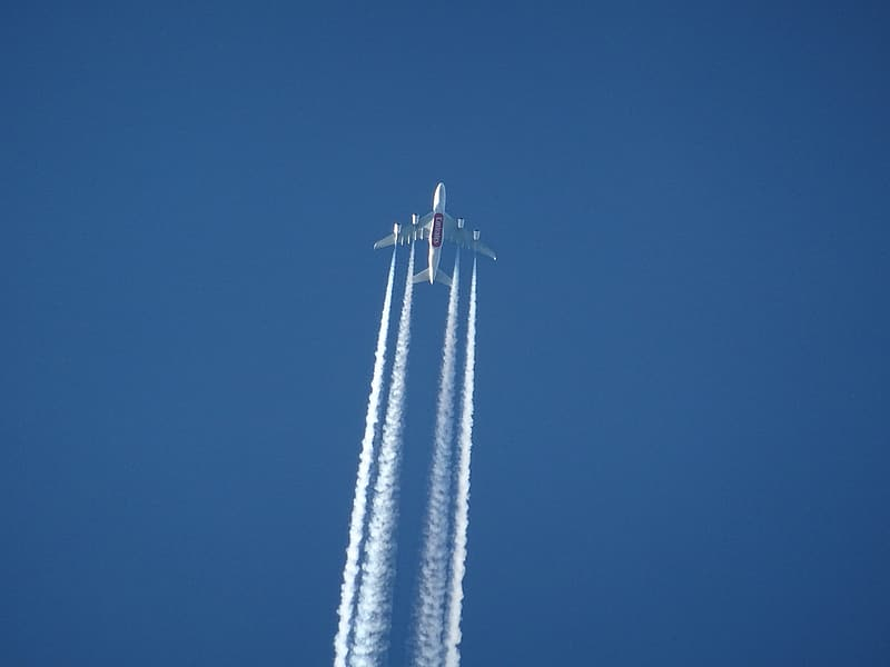 White airplane flying under clear blue sky