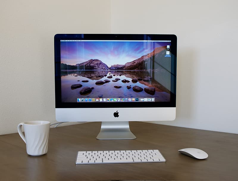 Silver iMac, magic keyboard, and magic mouse on top of brown wooden table