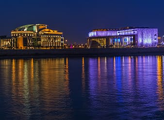 Two lighted buildings near body of water during nighttime