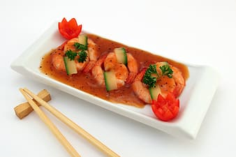 Shrimp with sauce in rectangular white ceramic tray and pair of brown chopsticks