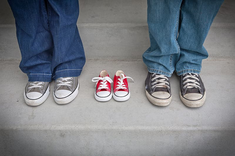 Two person wearing gray and black low-top sneakers