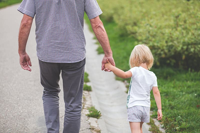 Man holding the hand of girl walking on road