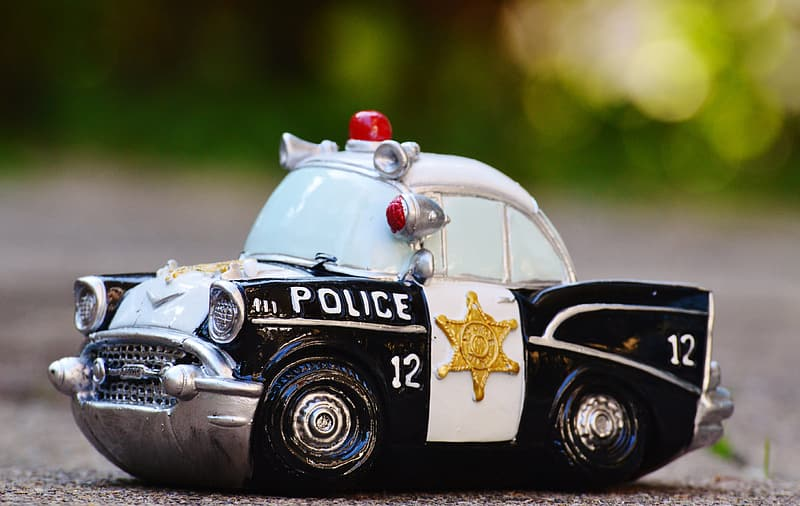 Selective focus photography of white and black police car scale model on pavement