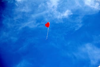 Red heart balloon on air