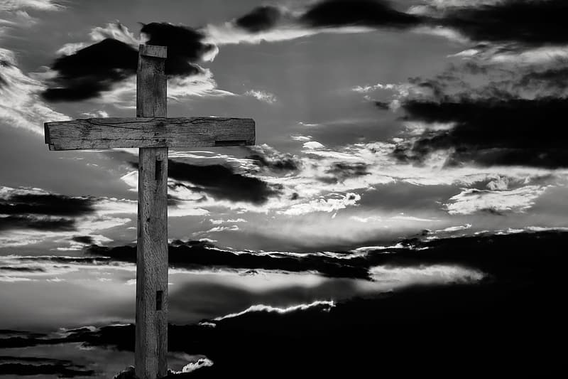 Cross under cloudy sky