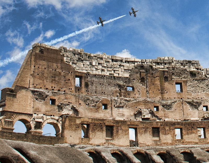 Closeup photography of brown Colosseum under two aircrafts