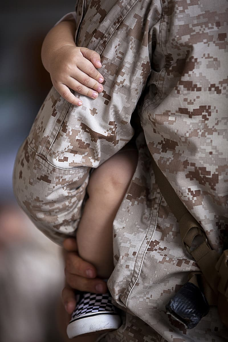 Close up photograph of man in military jacket holding baby