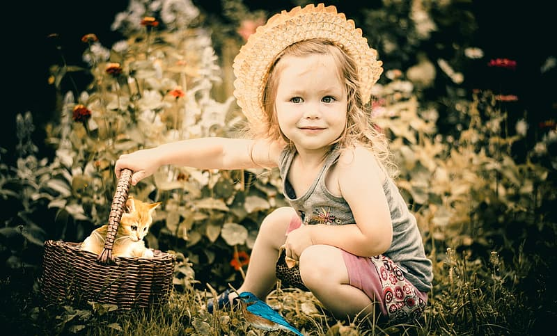 Girl in white and red floral dress wearing brown woven hat sitting on ground during daytime