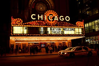 Group of people standing outside Chicago cinema theater during night time