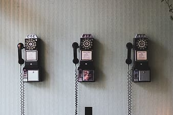 Three rotary telephones on white wall