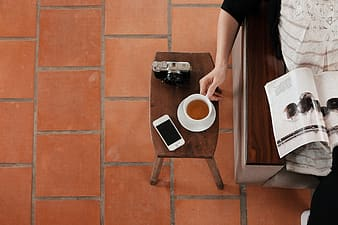 Person holding white ceramic mug and black dslr camera on brown wooden table