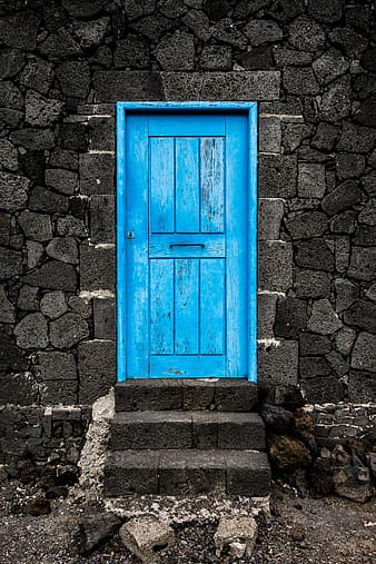 Blue wooden door on gray concrete structure