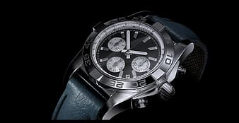 Closeup photo of round silver-colored chronograph watch with black leather band